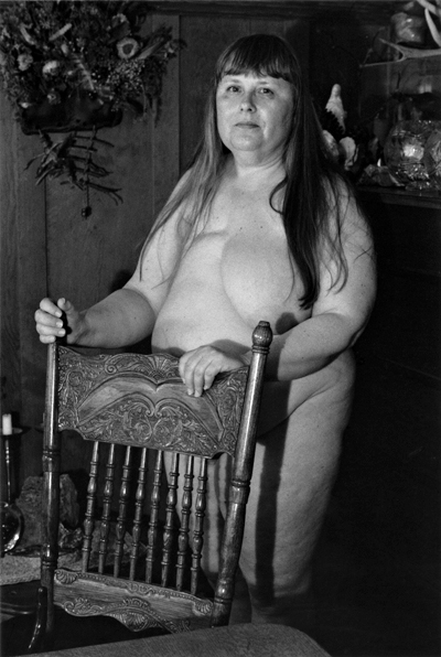 Woman with mastectomy behind railed chair