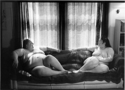 Two nude women  facing each other on a couch (from Women En Large)