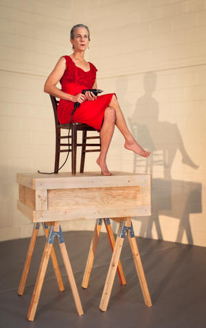 dancer sitting on chair holding a drill